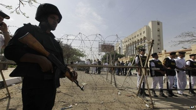Egyptian soldiers and police stand guard outside the election commission's headquarters in Cairo (19 April 2014)