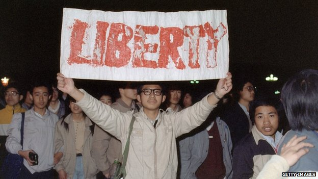 Student displays a banner with one of the slogans chanted by the crowd of some 200,000 pouring into Tiananmen Square 22 April 1989 in Beijing in an attempt to participate in the funeral ceremony of former Chinese Communist Party leader and liberal reformer Hu Yaobang during an unauthorized demonstration to mourn his death