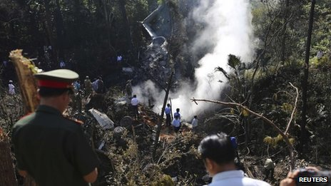 Rescue workers search an air force plane crash site near Nadee village, in Xiangkhouang province in the north of the country May 17, 2014