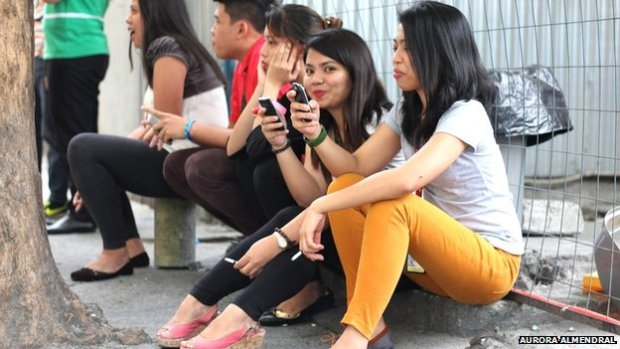 Group of Filipinos using mobile phones