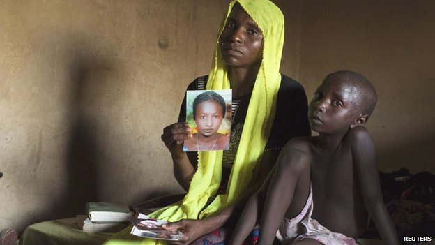 Rachel Daniel, 35, holds up a picture of her daughter abducted from the school in Chibok in April - next to her sits her seven-year-old son