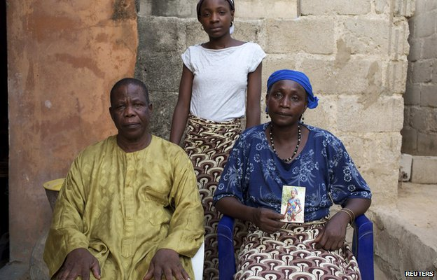 Chiroma Maina (R), holding a picture of her abducted daughter, sits next to her husband. Their other daughter stands behind them - Maiduguri, Nigeria - 21 May 2014