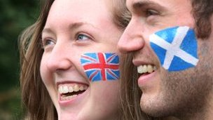 A woman with Union Jack face paint and a man with a Scotland flag