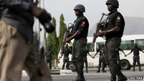 Police officers patrol near a journalist in Abuja, Nigeria (22 May 2014)