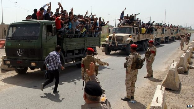 Iraqi men who volunteered to join the fight against ISIS's offensive run on board army lorries outside a recruitment centre in Baghdad (13 June 2014)