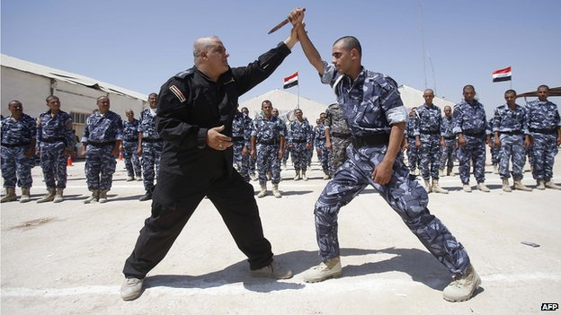 Newly-recruited Iraqi volunteers, wearing police forces uniforms, take part in a training session on June 17