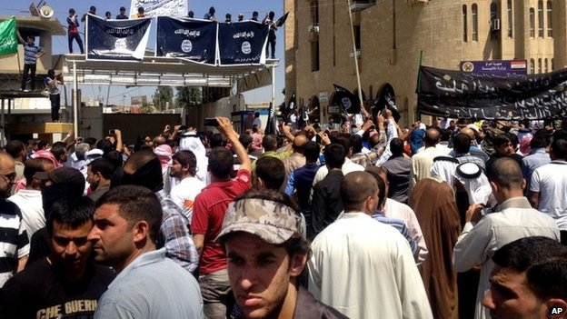 Islamic State of Iraq and the Levant supporters chant pro al-Qaeda slogans in front of the provincial government headquarters in Mosul, Iraq, Monday, June 16, 2014
