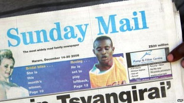 Someone holding up a copy of Zimbabwe's Sunday Mail paper from 2008
