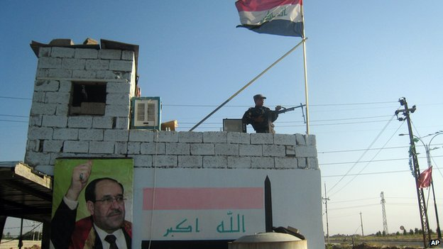 A member of the Iraqi security forces stands guard at the entrance checkpoint of the Bansher district, near the oil-rich city of Kirkuk, Iraq, on 20 June 2014