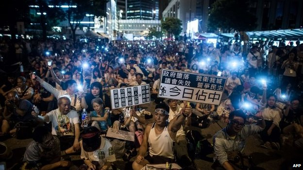 Demonstrators sit in a street of the central district after a pro-democracy rally seeking greater democracy in Hong Kong on 1 July 2014