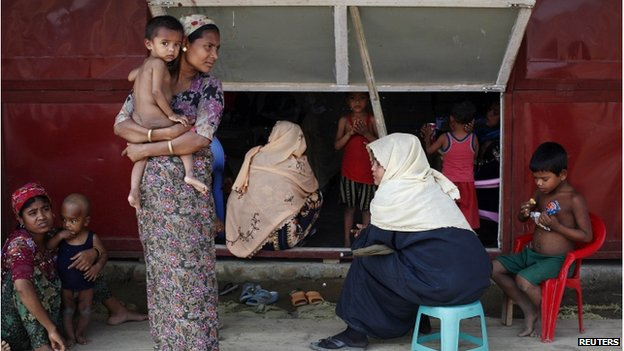 Rohingya women and their children wait to receive treatment at a makeshift clinic in the Thet Kae Pyin camp for internally displaced people in Sittwe, Rakhine state, 24 April 2014.