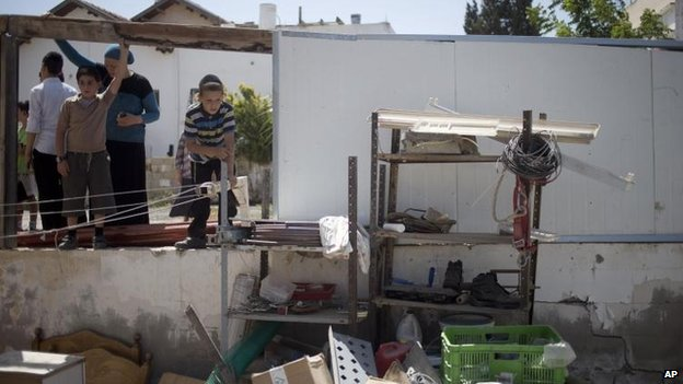 Residents of Netivot look at the damage caused by a Palestinian missile strike, 10 July