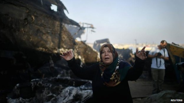 A Palestinian woman reacts after her son's boat is burned in an Israeli naval strike in Gaza City, 11 July