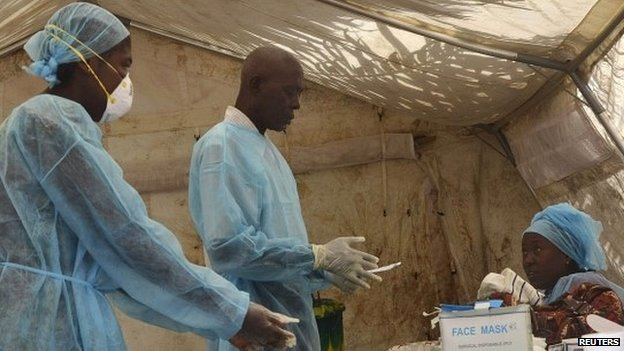 Health workers take blood samples for Ebola virus testing at a screening tent in the local government hospital in Kenema, Sierra Leone - 30 June 2014