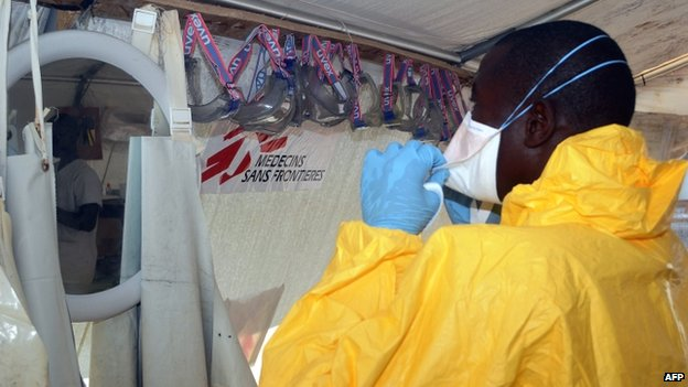 An MSF employee puts on protective gear at the isolation ward of the Donka Hospital in Conakry, where people infected with the Ebola virus are being treated - June 2014