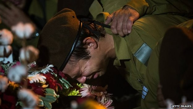 An Israeli soldier weeps over the casket of Private First Class Jordan Bensimon during his funeral in Ashkelon, Israel, 22 July 2014