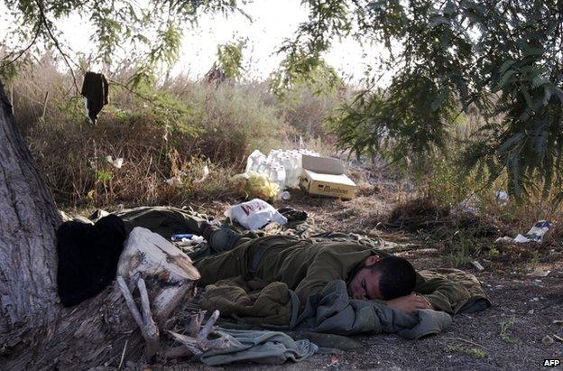 An Israeli soldier sleeps on the border with Gaza, 28 July