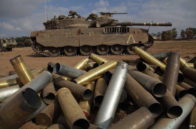 Empty shells beside an Israeli tank near the Gaza border, 28 July
