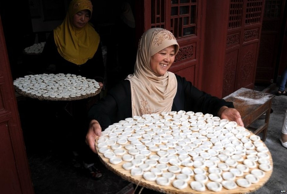 """Muslims prepare food as they gather in a mosque to celebrate Eid al Fitri in Tancheng, east China""""s Shandong province on July 29, 2014"""