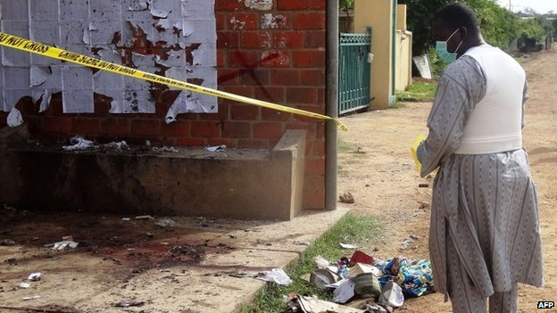 A police detective inspects the site of a suicide blast in the northern Nigerian city of Kano on 30 July 2014