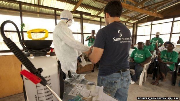 A member of the Samaritan's Purse medical staff demonstrates personal protective equipment to educate volunteers on the Ebola virus in Liberia