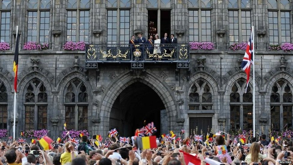 Prince Harry, Mons city mayor Nicolas Martin, Prince William and the Duchess of Cambridge appear on a balcony at the Mons townhall with Belgium's outgoing Prime Minister Elio Di Rupo