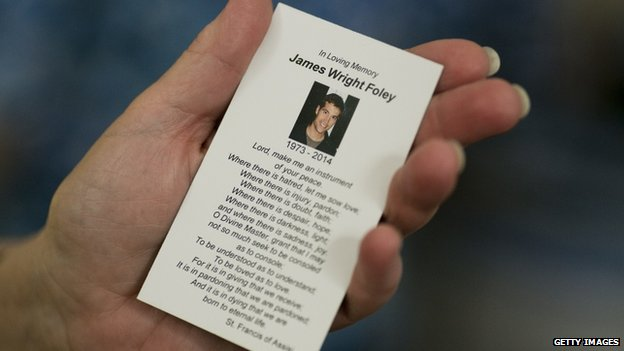 parishioner holds a prayer card in memory of James Foley after a Catholic mass in Rochester, New Hampshire