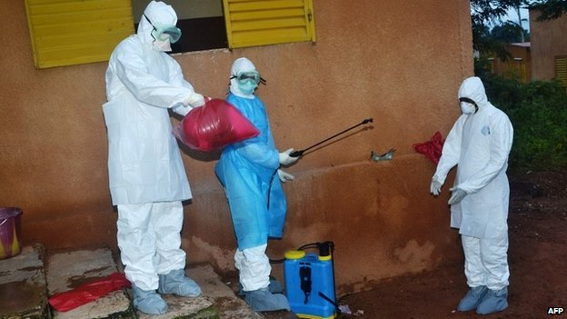 Health workers take off their protective suits after finishing disinfecting areas at a hospital in Pita, Guinea - 25 August 2014
