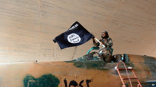 Islamic State fighter waves flag from fighter jet at Tabqa air base. 27 Aug 2014