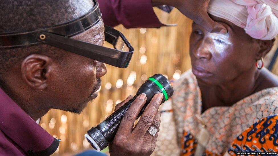 Eye surgeon Boubacar Fomba examining Kany Doumbia' eyes in N'Korobougou, Mali