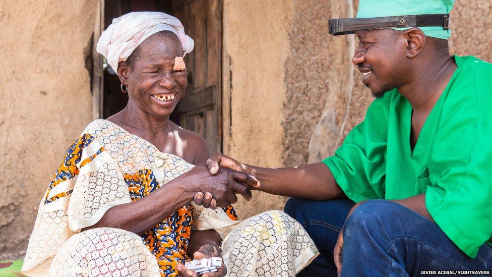 Eye surgeon Boubacar Fomba shakes Kany Doumbia's hands in N'Korobougou, Mali