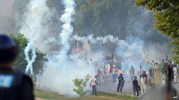 Pakistani protesters stand amongst tear gas during clashes with police in Islamabad. Photo: 31 August 2014