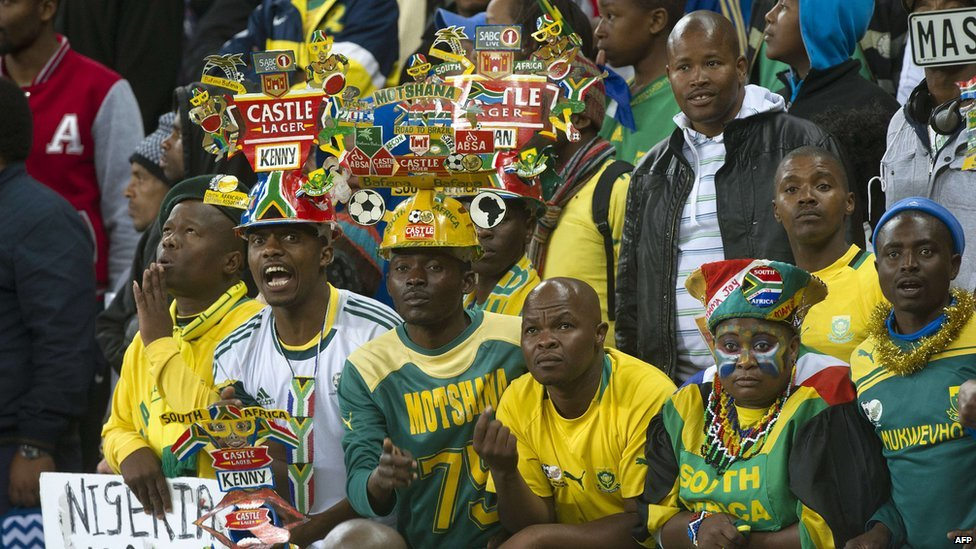 Fans of South Africa's football team, some of them wearing Makarapa hats, cheer during the 2015 African Cup of Nations qualifying football match between South Africa and Nigeria on 10 September 2014 in Cape Town, South Africa