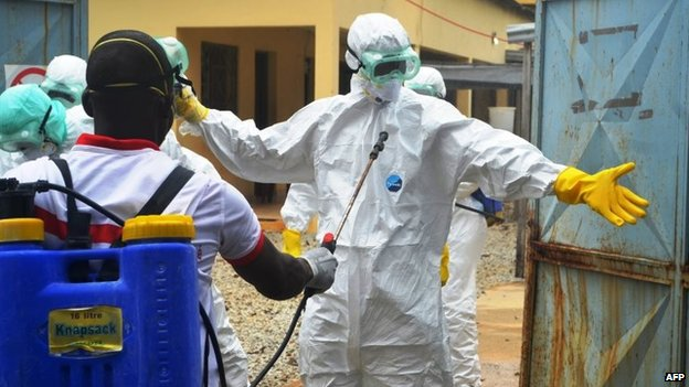 Guinea's Red Cross health workers wearing protective suits prepare to carry the body of a victim of Ebola at the NGO Medecin Sans Frontieres Ebola treatment centre near the hospital Donka in Conakry, 14 September 2014