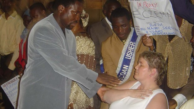 TB Joshua attending to a follower