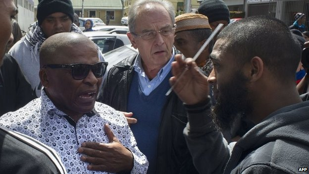 A Muslim man (R) argues with people going to the opening of the Open Mosque, on September 19, 2014 in Wynberg, Cape Town.