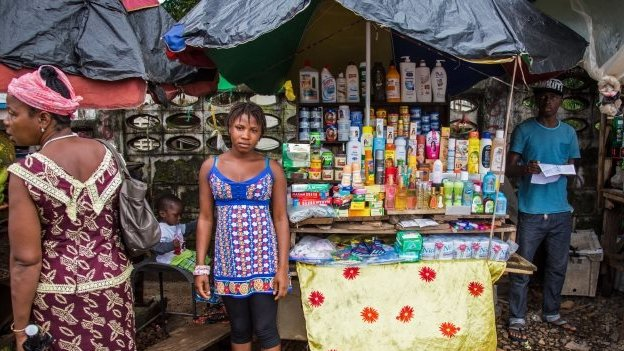 A vendor stands among her goods in Freetown, Sierra Leone, Thursday, 18 September 2014