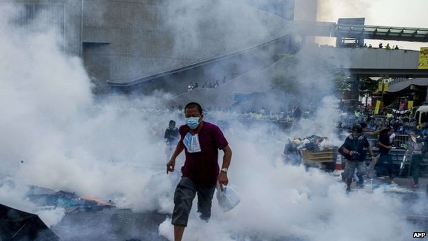 A pro-democracy demonstrator runs as police fired tear gas towards protesters near the Hong Kong government headquarters on 28 September 2014