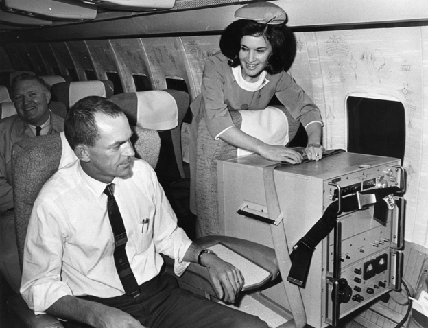 Two first class seats aboard a TWA jet from London to Washington. One occupied by a caesium beam timepiece accurate to one-millionth of a second used in the USA's space programme. This clock is being returned to America from South Africa and as it must not be allowed to stop it is connected to a power point in the aircraft during the flight. The other seat is occupied by one of the clock's escorts
