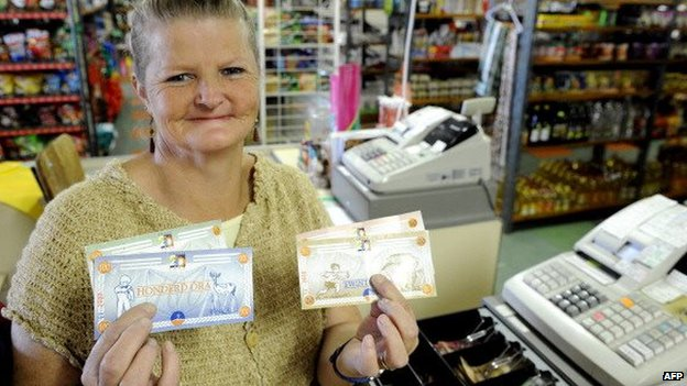 A woman holding Ora notes in Orania, South Africa