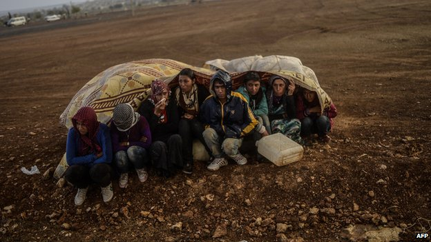 Syrian Kurds take cover from rain in Suruc after crossing border between Syria and Turkey 30 Sept 2014