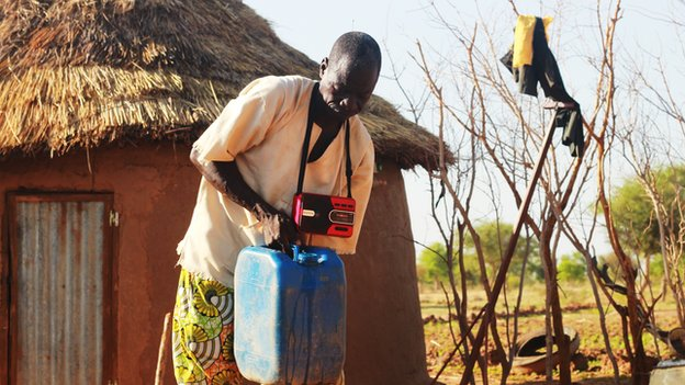 Man with portable radio hanging from his neck, carrying a water can in front of a mud hut