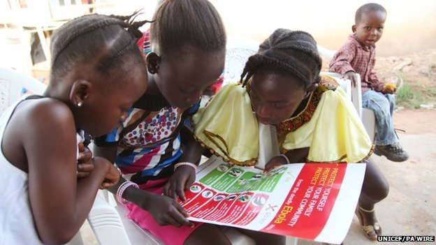 Girls look at a Unicef poster on how to prevent the spread of Ebola
