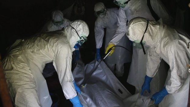 A burial team from the Liberian Red Cross sprays disinfectant over the body bag of an Ebola victim while collecting the man his home on 8 October 2014 near Monrovia, Liberia