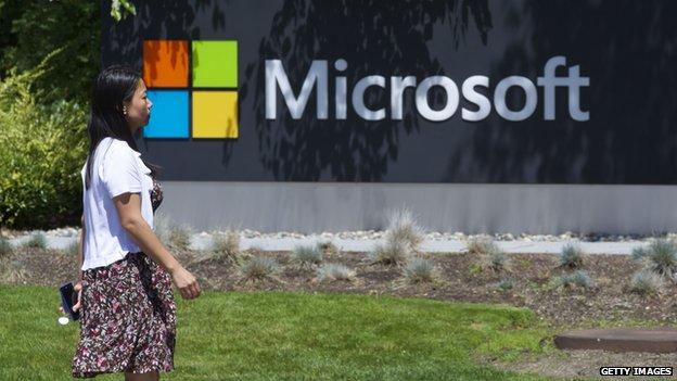 Una donna cammina di fronte a un segno di Microsoft su Washington campus della società.