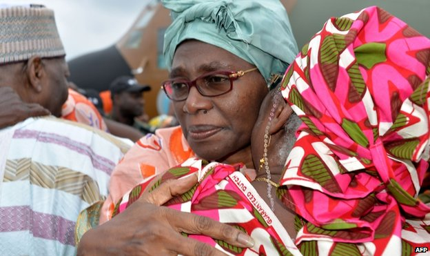 Akaoua Babiana, the wife of Cameroon's deputy prime minister, hugs a relative upon her arrival in Yaounde on 11 October 2014