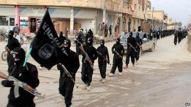 Islamic State militants march with the IS flag in Raqqa Syria on Jan 2014
