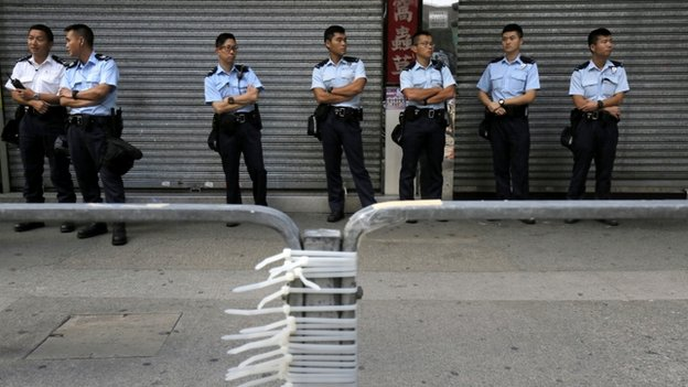 Police officers stand guard after removing barricades that protesters have set up to block off main roads in Causeway Bay district in Hong Kong