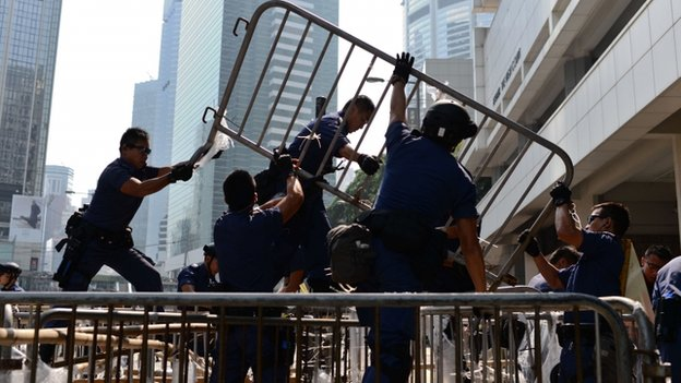 Police officers remove barricades during a pro-democracy protest in the Admiralty district of Hong Kong on October 14, 2014