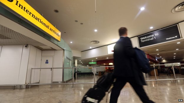 Passengers arrive at Terminal 1 of Heathrow Airport amid enhanced screening for Ebola on 14 October 2014.